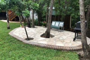 large custom stone patio with bench and bbq area
