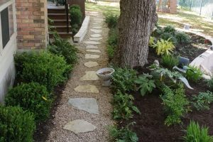 stone pathway surrounded by fresh plant and flower landscaping