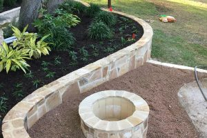 Custom stone retaining wall with plant and flower beds