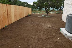 new fence installation and fresh dirt for landscaping