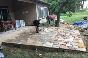 two men working on a large stone patio project